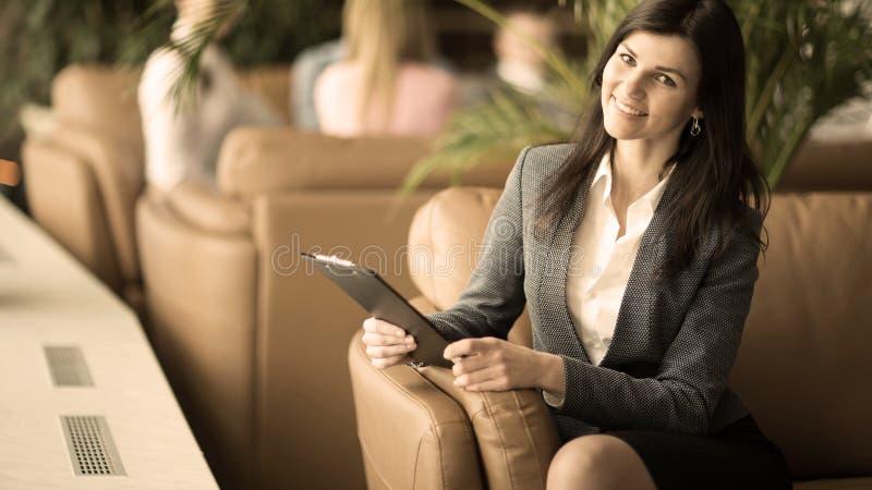 有坐在一个现代办公室的大厅的一把椅子的文件的成功的女商人 免版税图库摄影