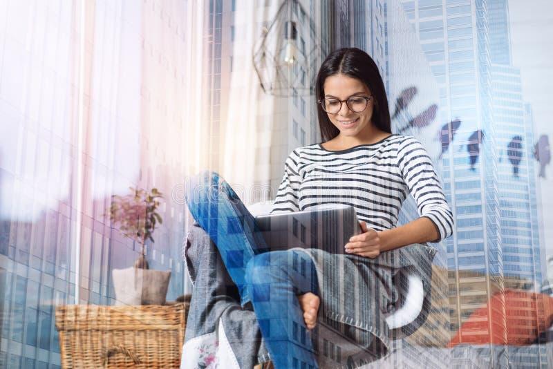 有坐在一把舒适的扶手椅子的一种现代片剂的快乐的妇女 库存图片
