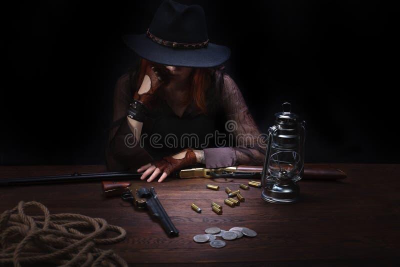 有坐在与弹药和银币的桌上的左轮手枪枪的野生西部女孩 库存照片