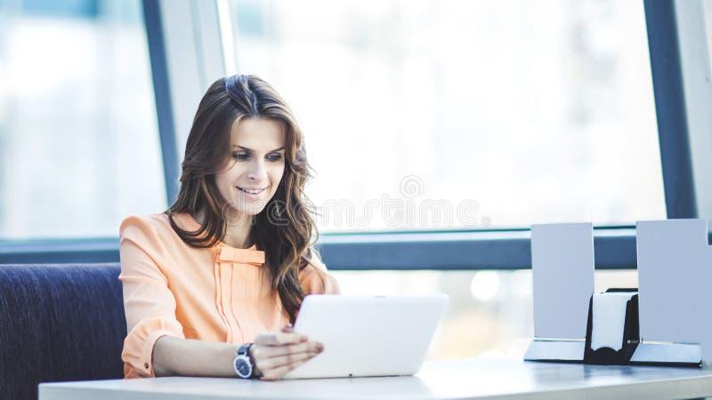 有坐在书桌的数字式片剂的成功的女商人在宽广的办公室 库存图片