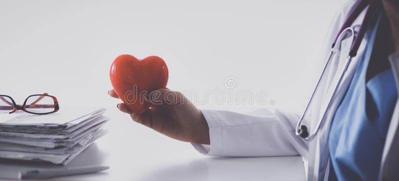 有坐在书桌的红色心脏标志的年轻医生 免版税库存图片