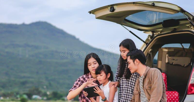 有坐在享受的旅行和暑假汽车的亚洲家庭的愉快的女孩在露营者货车 免版税库存照片