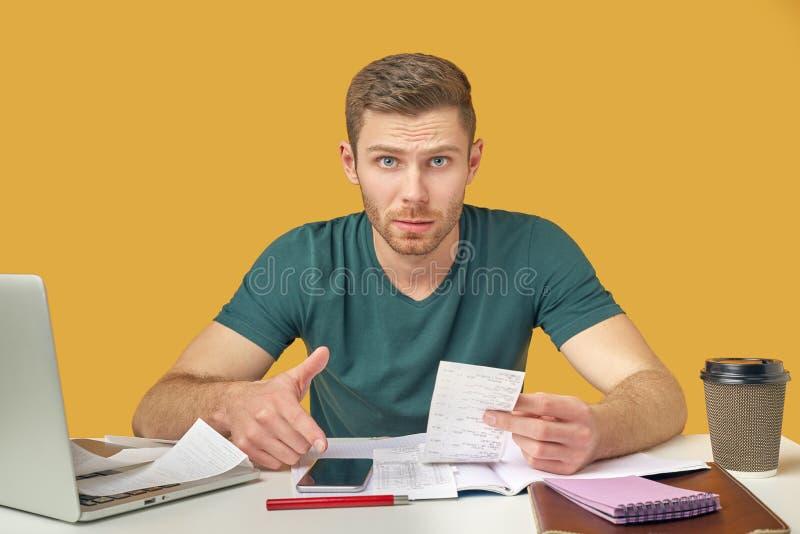 有坐在他的有膝上型计算机和电话的书桌的胡子的好人 在疑惑地他的手、一检查从商店和神色上 免版税库存图片