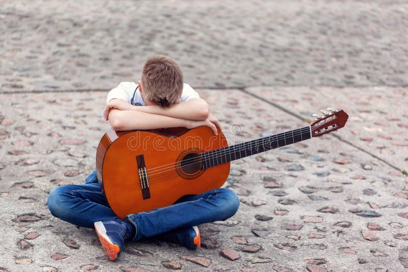 有坐在公园的声学吉他和耳机的少年 库存图片
