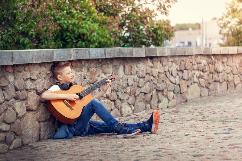 有坐在公园的声学吉他和耳机的少年 图库摄影