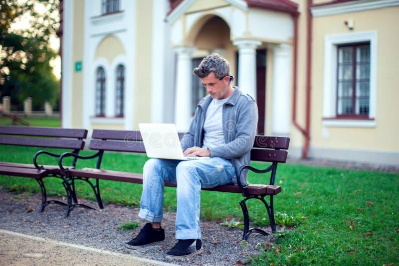 有坐在公园的膝上型计算机的年轻人 人们,技术co 免版税库存图片