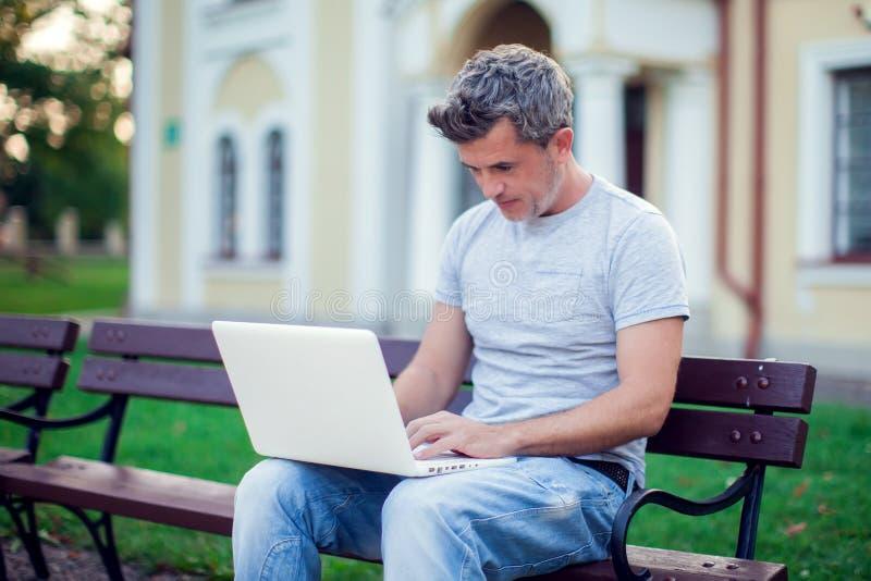 有坐在公园的膝上型计算机的年轻人 人们,技术co 图库摄影