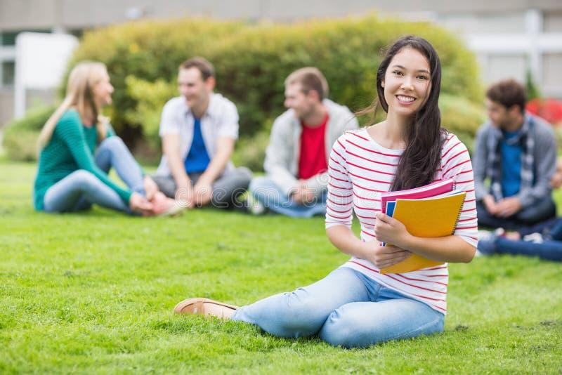 有坐在公园的被弄脏的朋友的微笑的大学生 免版税库存照片