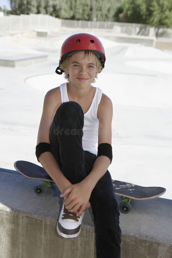 有坐在冰鞋公园的滑板的十几岁的男孩 免版税库存图片