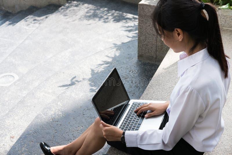 有坐在办公楼之外的膝上型计算机的女实业家 年轻 库存照片