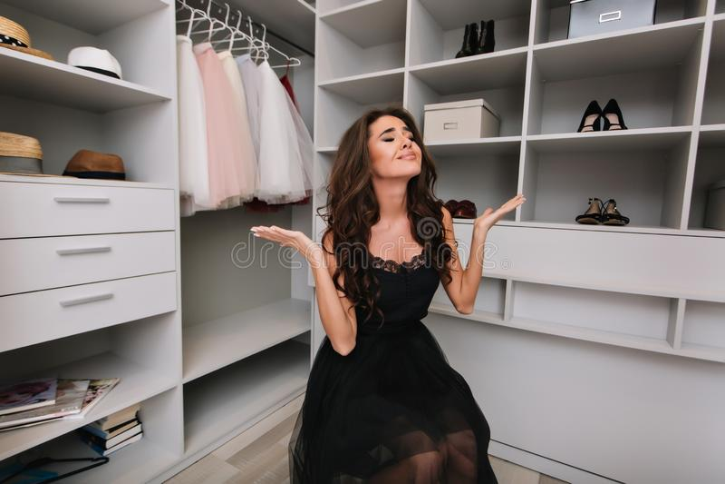 有坐在化装室,衣橱的棕色卷发的美丽的年轻女人,失望,弄翻,难做出选择 图库摄影