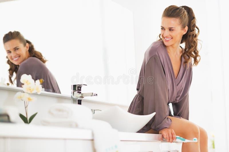 有坐在卫生间里的牙刷的微笑的妇女 免版税图库摄影