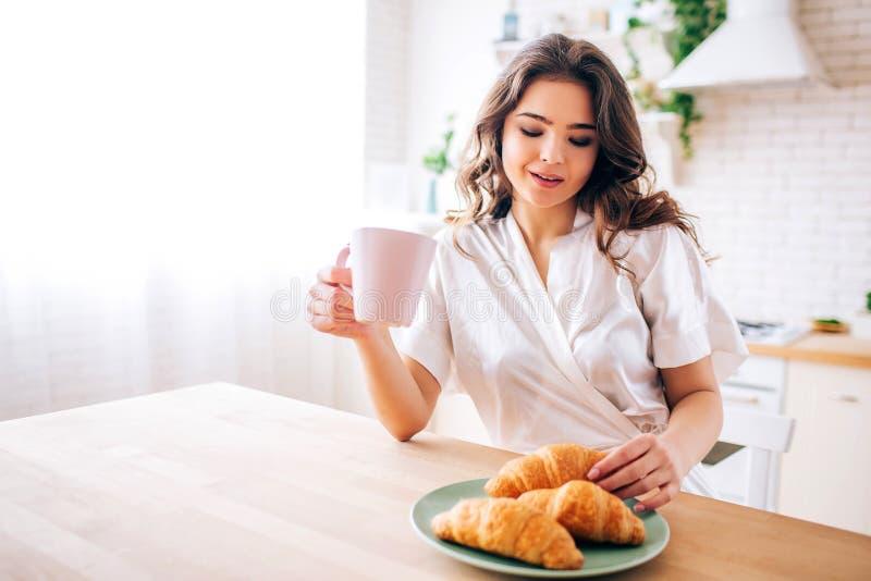 有坐在厨房和饮用的咖啡里的黑发的年轻女人在早晨 采取一新月形面包和微笑 令人愉快 库存图片