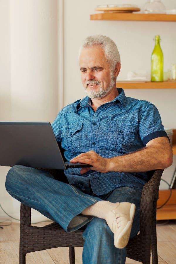 有坐在厨房的笔记本的老人 免版税图库摄影