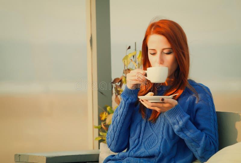 有坐在咖啡馆的杯子的女孩在沿海附近 库存图片