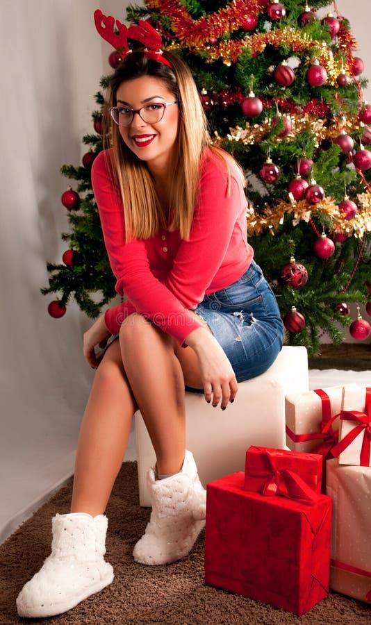有坐在圣诞树和礼物盒前面的驯鹿和裙子垫铁的愉快的女孩  图库摄影