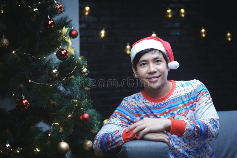 有坐在圣诞树旁边的圣诞节服装的亚裔人 库存照片