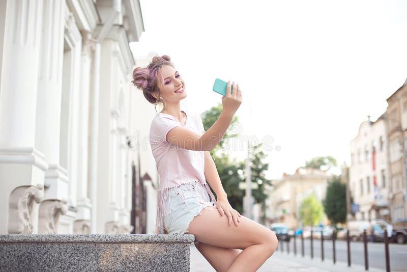 有坐在城市背景中的桃红色头发的愉快的快乐的年轻金发碧眼的女人拍照片的她自己与机动性 图库摄影