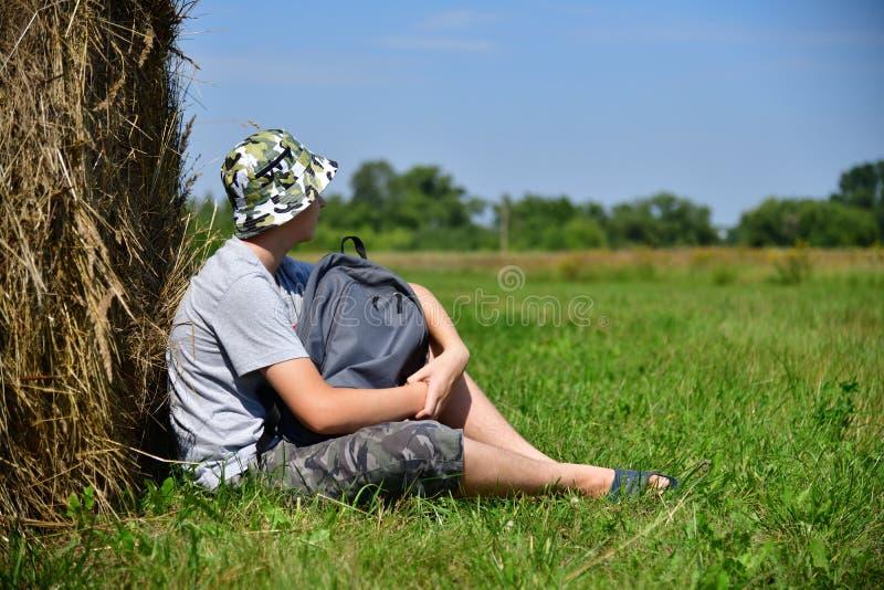 有坐在堆的背包的少年秸杆旁边 免版税库存照片
