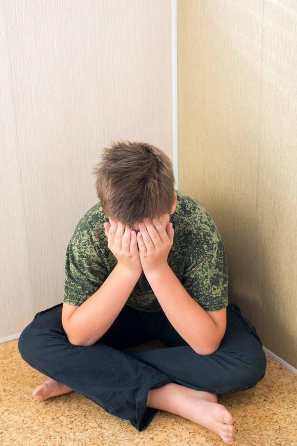 有坐在室的角落的消沉的男孩少年 库存图片