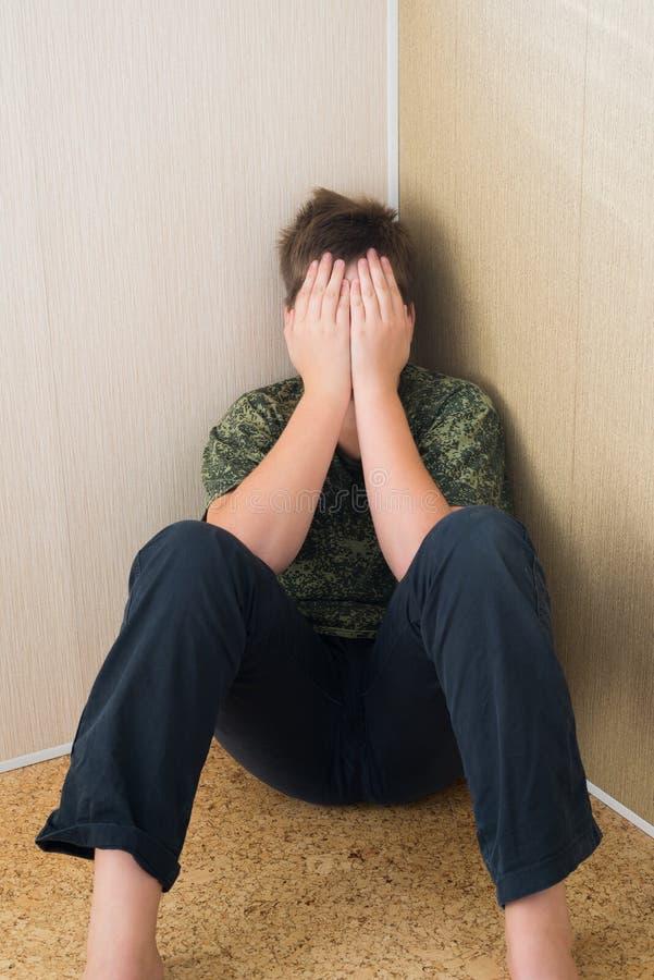 有坐在室的角落的消沉的男孩少年 免版税图库摄影