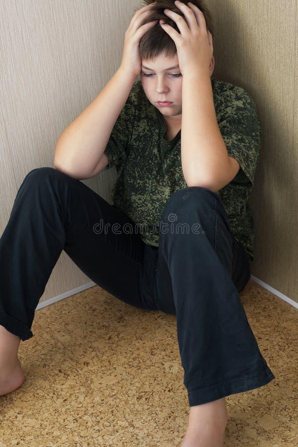 有坐在室的角落的消沉的男孩少年 免版税库存照片