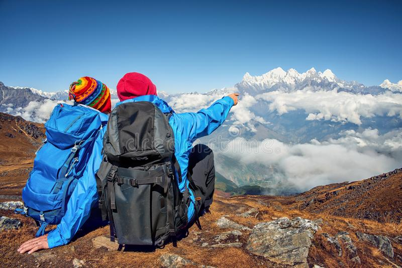 有坐在山,谈论顶部的背包的远足者 免版税库存照片
