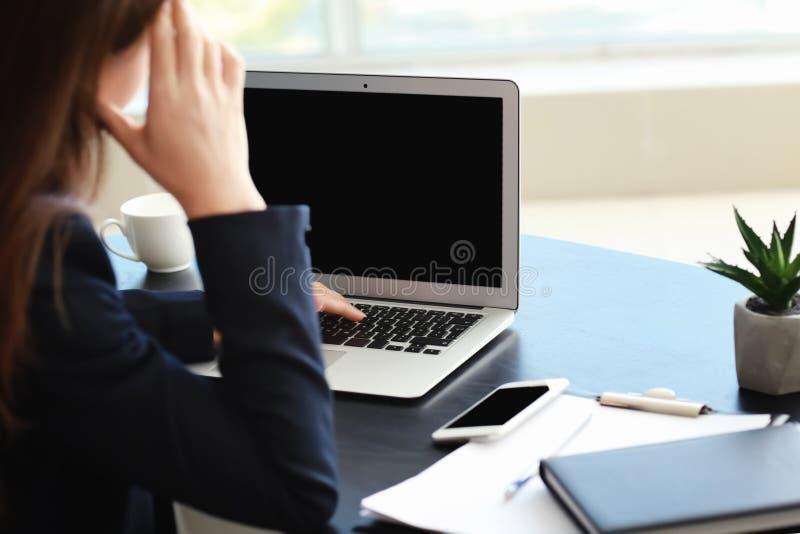 有坐在工作场所的非工作的膝上型计算机的被注重的女实业家在办公室 图库摄影