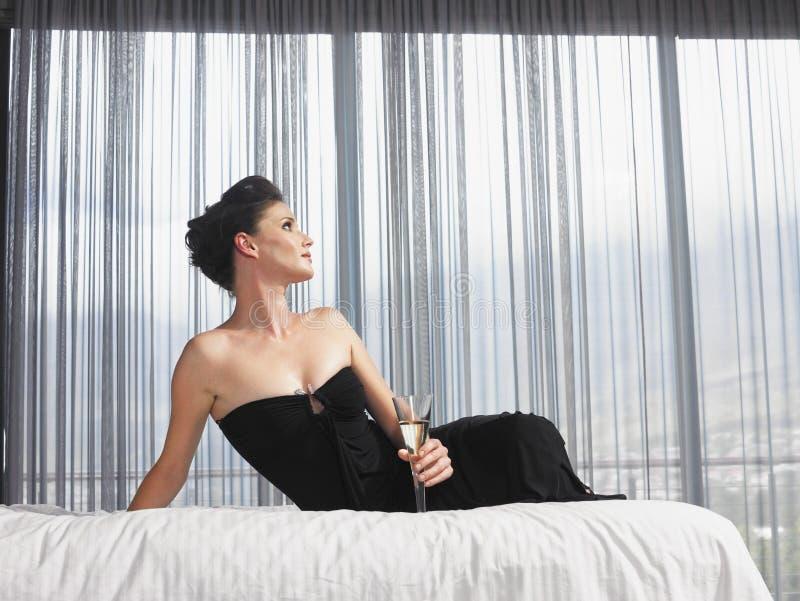 有坐在床上的香宾玻璃的端庄的妇女 免版税库存照片