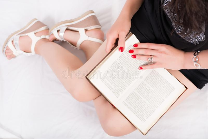 有坐在床和读上的书的有吸引力的女性腿 免版税库存图片