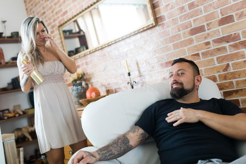 有坐在扶手椅子和妇女的纹身花刺的人饮用金黄瓶香槟在背景 库存照片