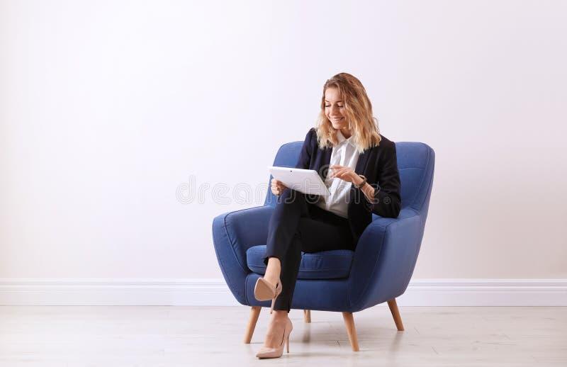 有坐在扶手椅子的片剂的年轻女人 库存图片