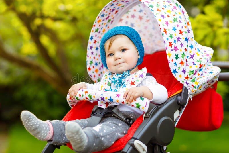 有坐在摇篮车或婴儿推车和等待妈妈的蓝色温暖的帽子的逗人喜爱的健康矮小的美丽的女婴 ?? 图库摄影