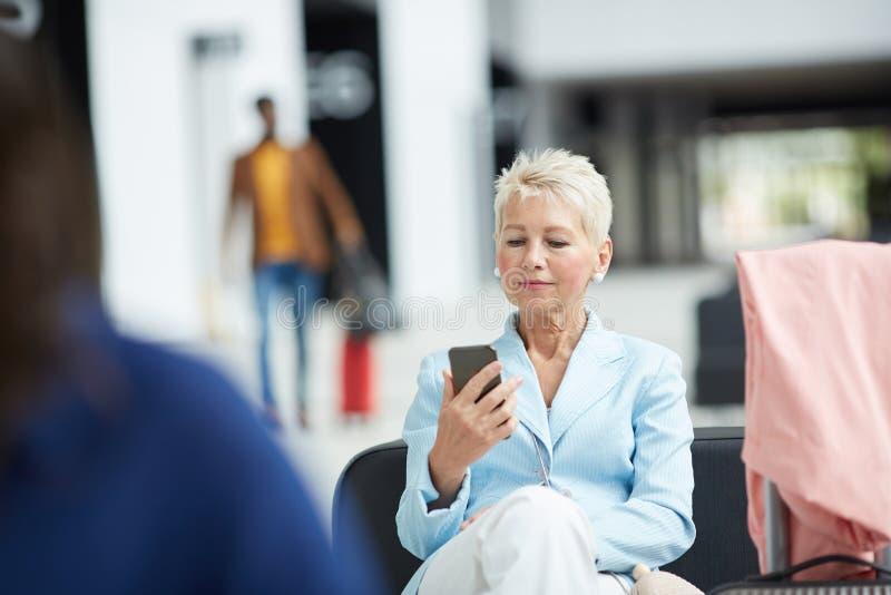 有坐在机场的构成的成熟妇女 库存照片