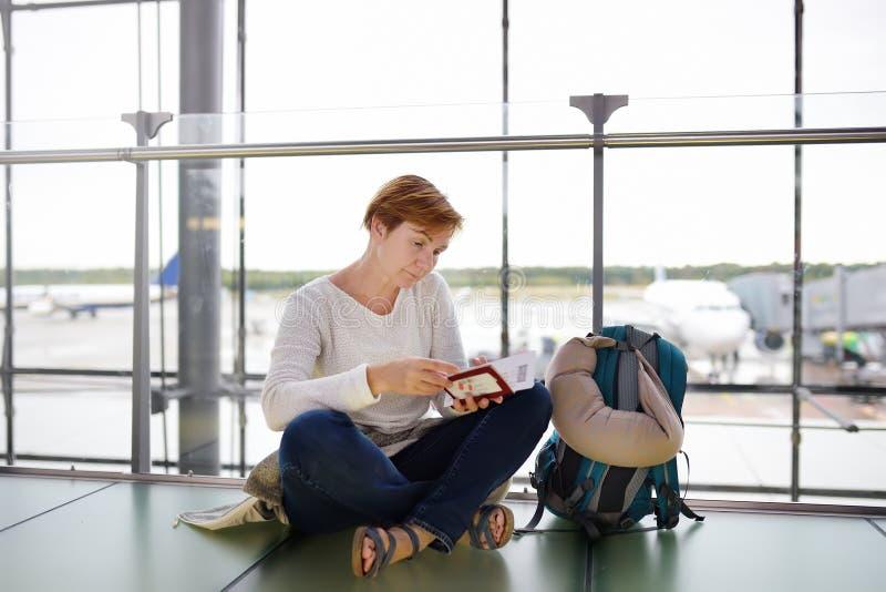 有坐在机场的等候室和检查她的票的背包和旅行枕头的成熟妇女 库存照片
