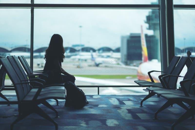 有坐在机场的背包的一个妇女旅客 库存图片