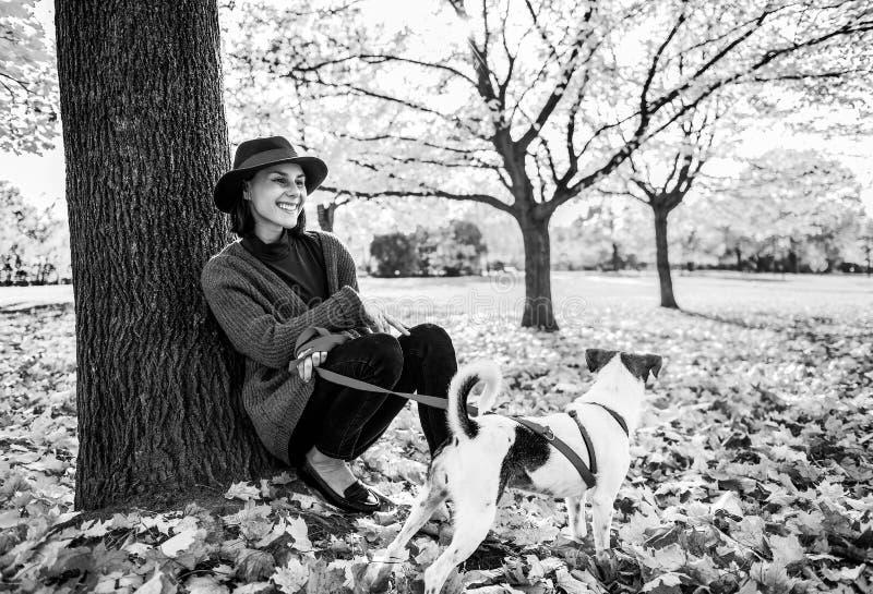 有坐在树下的逗人喜爱的狗的少妇在秋天公园 库存图片