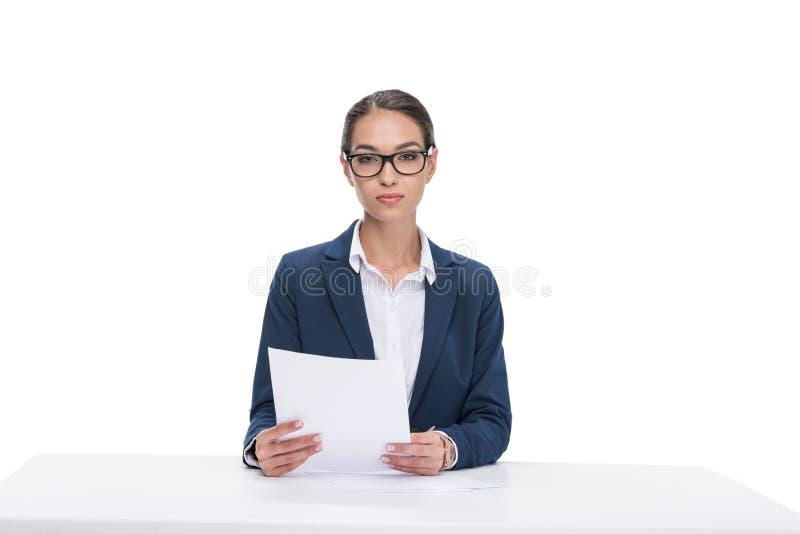 有坐在桌上和看照相机的纸的美丽的女性新闻广播员, 免版税库存照片