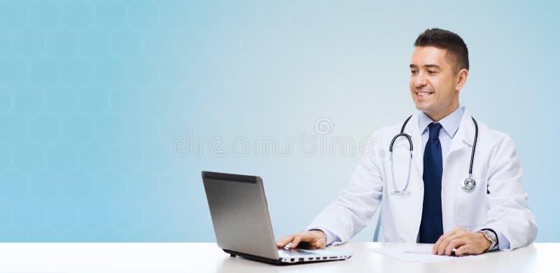 有坐在桌上的膝上型计算机的微笑的男性医生 免版税库存照片