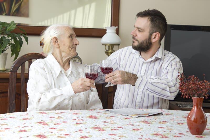 有坐在桌和多士上的孙子的祖母拿着一杯红葡萄酒 库存照片