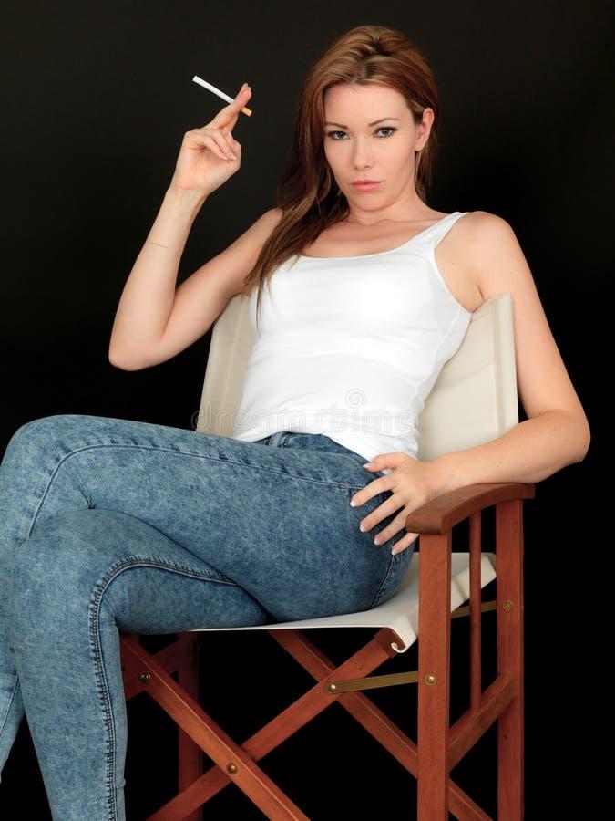 日本成人少妇xx故事_有坐在椅子的态度的美丽的少妇拿着未点燃的香烟