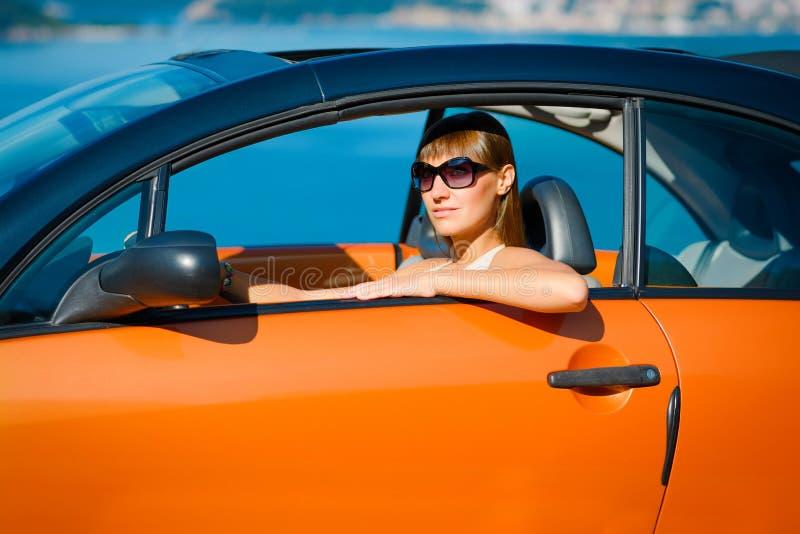 有坐在橙色敞蓬车的长发的美丽的年轻女人在陆间海海岸 库存照片