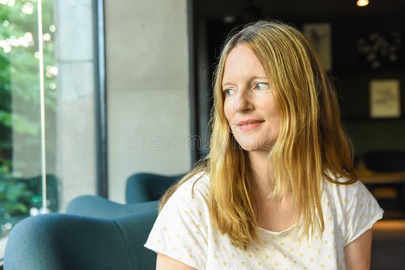 有坐在欧洲美国咖啡馆休息室的石楠金发蓝眼睛的美丽的年轻白种人妇女看在窗口 库存照片