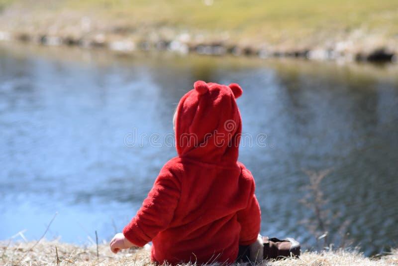 有坐在池塘前面的红色外套的小孩 免版税库存图片