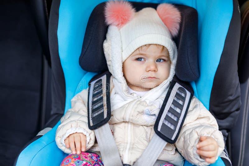 有坐在汽车座位的蓝眼睛的可爱的女婴 小孩孩子在冬天给继续穿衣家庭度假和 库存图片