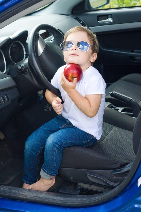 有坐在汽车的玻璃和红色苹果的男孩 免版税库存照片