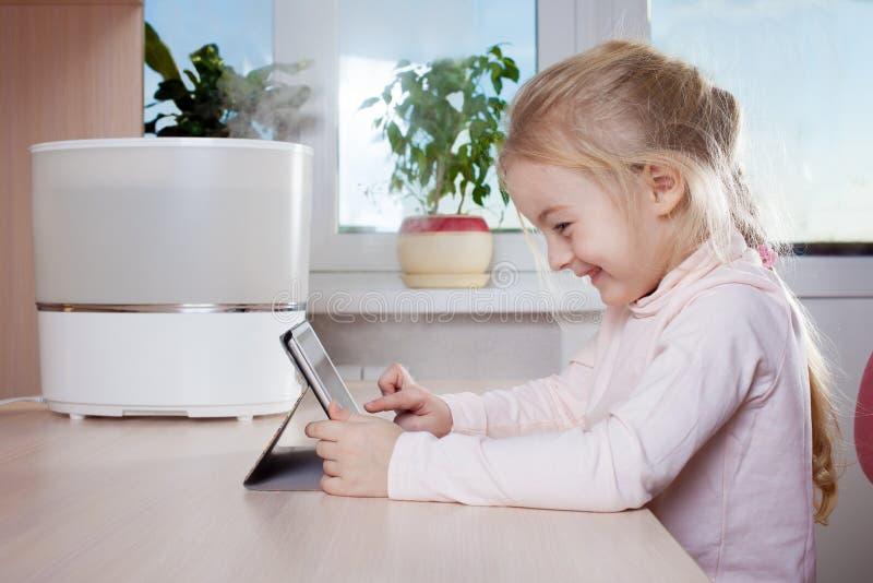 有坐在润湿器和微笑附近的片剂个人计算机的小女孩 库存照片