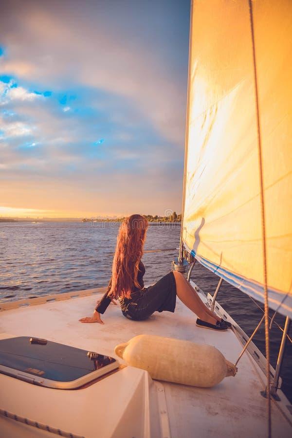 有坐在游艇和神色的船尾的长的头发的女孩入距离在日落 库存图片