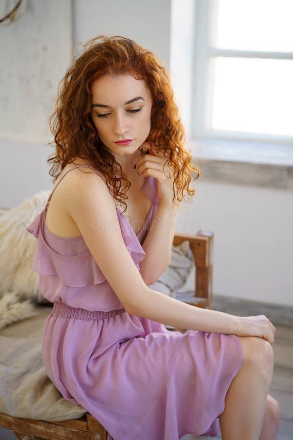 有坐在演播室的红色头发的美丽的年轻女人 免版税库存照片