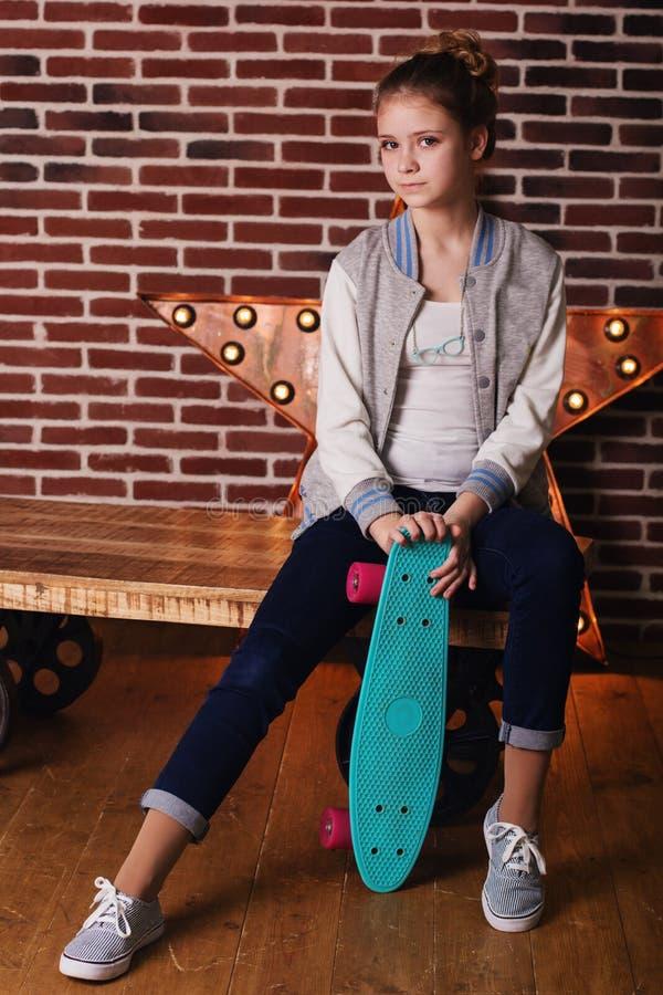 有坐在演播室的滑板的俏丽的少年女孩 免版税库存照片